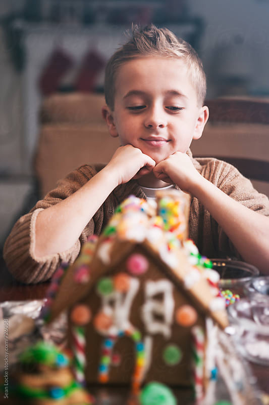 Christmas: Boy Admires His Gingerbread House by Sean Locke for Stocksy United