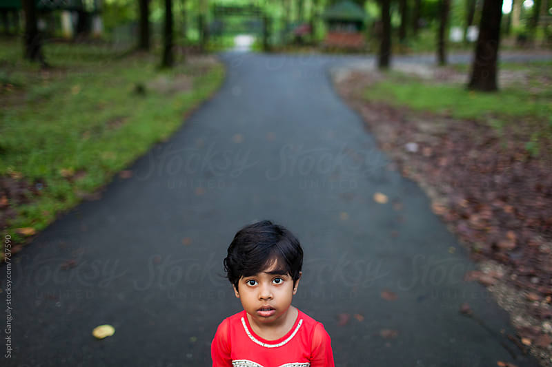 Cute little girl looking at camera with a blank expression by Saptak Ganguly for Stocksy United
