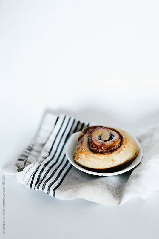 Cinnamon bun on cloth on white background by Treasures & Travels for Stocksy United