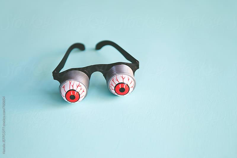 joke bloodshot eye glasses on a blue table top by Natalie JEFFCOTT for Stocksy United