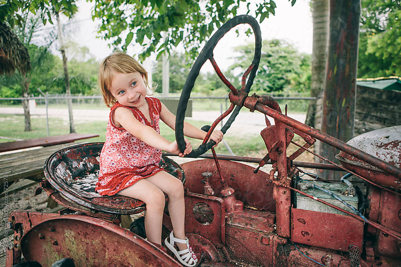 Little Girl Driving Old Tractor by Stephen Morris for Stocksy United
