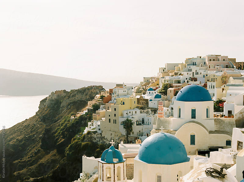 View of Oia, Santorini with traditional blue church domes by Kirstin Mckee for Stocksy United