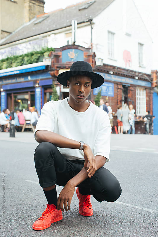 London Street Style - Cool Young Fashionable Black Man Crouching Down in Busy Street by Julien L. Balmer for Stocksy United
