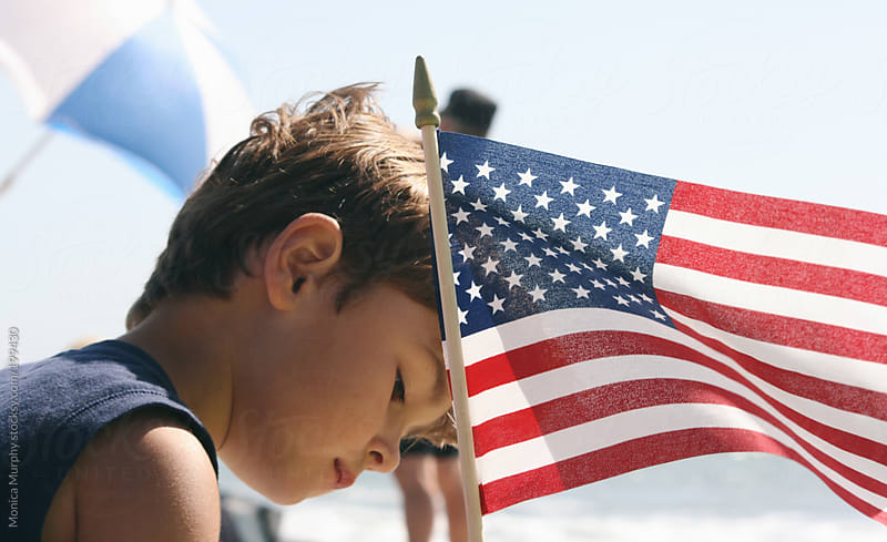 Young boy with American Flag on the beach by Monica Murphy for Stocksy United