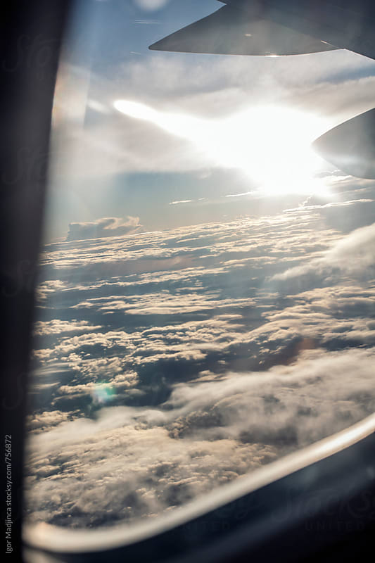 view through the airplane window,sun ray a beautiful white clouds after a storm by Igor Madjinca for Stocksy United