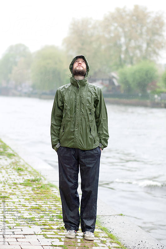 A young man with a beard standing in the rain next to a canal, looking up in the sky by Ivo de Bruijn for Stocksy United