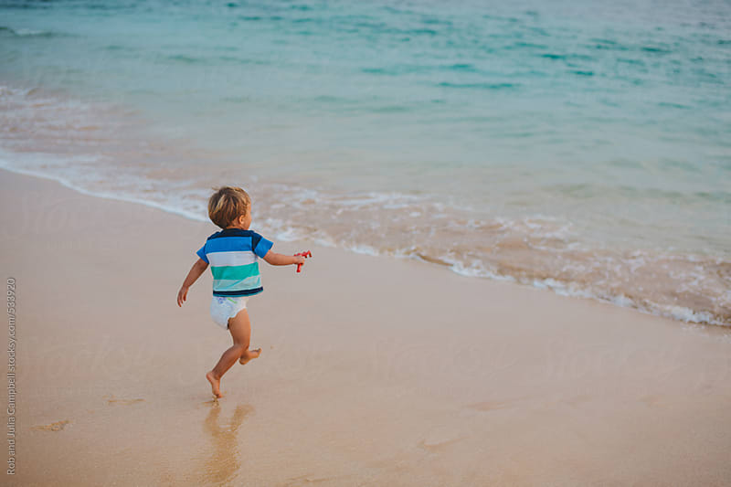 Cute toddler boy running toward ocean on tropical beach at sunset by Rob and Julia Campbell for Stocksy United