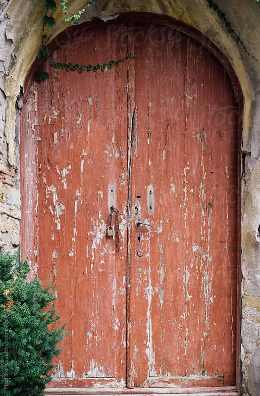 Red weathered door by Pixel Stories for Stocksy United