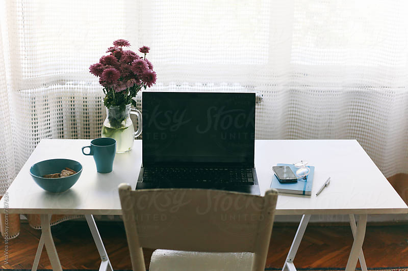 Laptop, notebook, smart phone and flowers on a white working desk  by VeaVea for Stocksy United