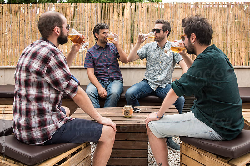 Friends drinking beer on a bar by Bisual Studio for Stocksy United