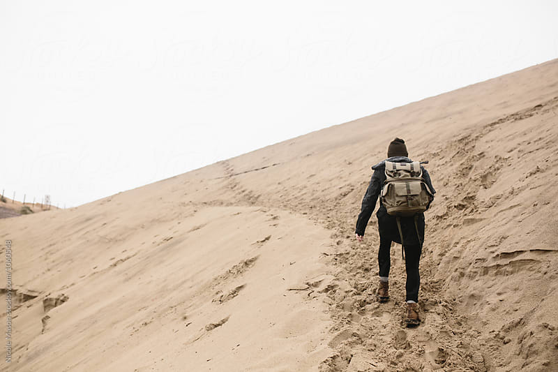 woman wearing backpack hiking up sand dune by Nicole Mason for Stocksy United