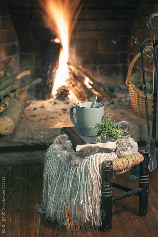Cozy home. A cup of coffee, book and blanket in a stool on front fireplace. by BONNINSTUDIO for Stocksy United