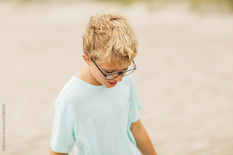 portrait of a boy wearing glasses looking down by Kelly Knox for Stocksy United