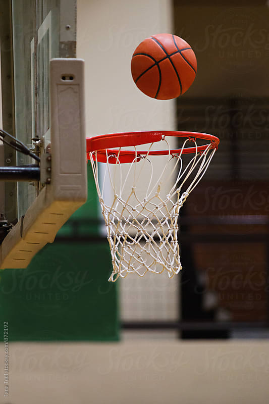 basketball floats above net  by Tana Teel for Stocksy United
