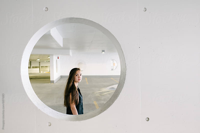 Portrait of a young woman through a circular cut out in wall by Preappy for Stocksy United