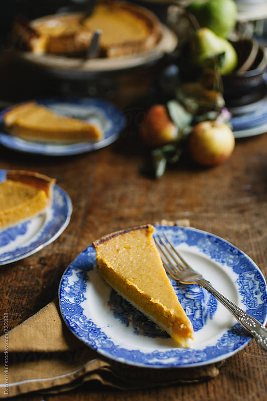 Pumpkin pie of blue plates on wooden table. by Darren Muir for Stocksy United