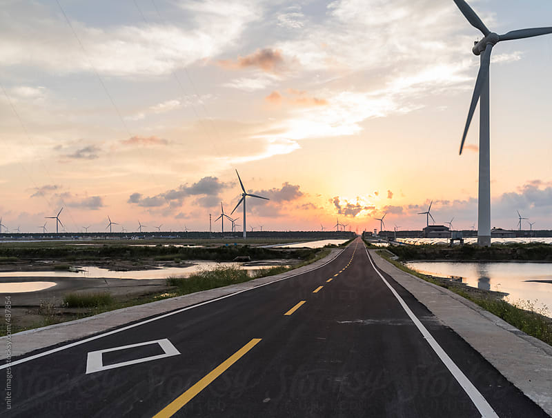 road through the wind turbines by unite images for Stocksy United