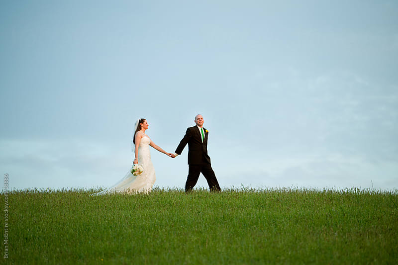Wedding: Bride and Groom Holding Hands on Hilltop by Brian McEntire for Stocksy United