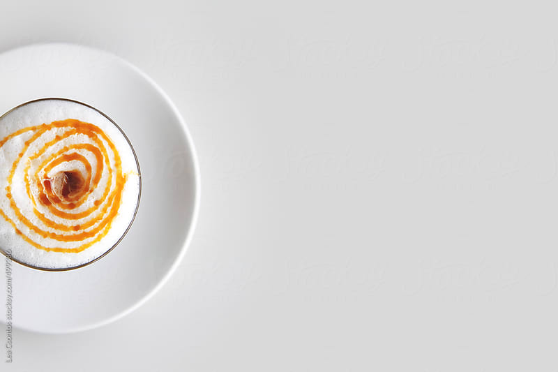 Latte macchiato with milk froth and caramel topping. Shot from above, positioned on the left. by Lea Csontos for Stocksy United