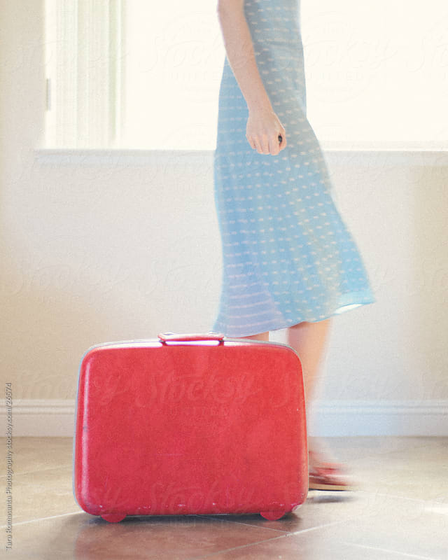 woman in a blue dress walking past a red suitcase by Tara Romasanta for Stocksy United