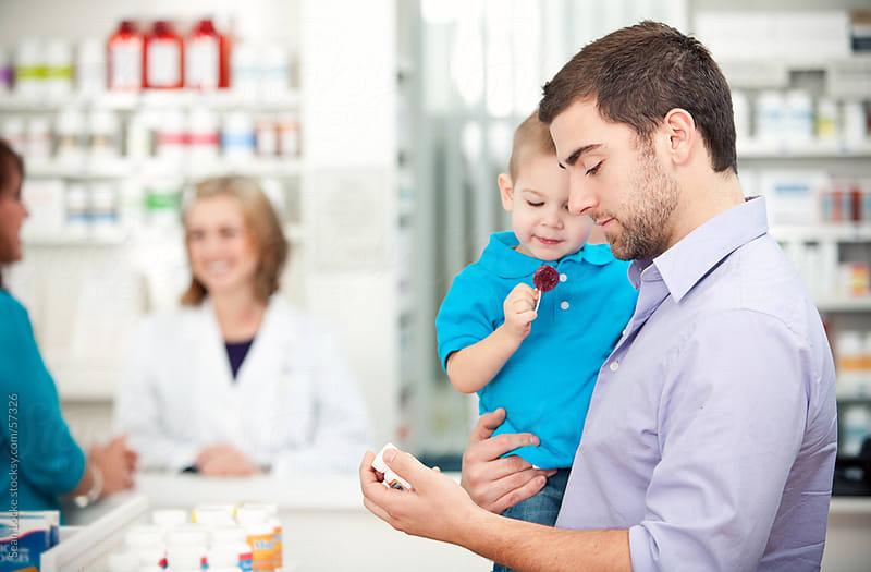 Pharmacy: Father Carrying Boy in Pharmacy by Sean Locke for Stocksy United