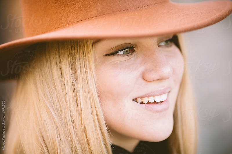 happy blond young woman with hat.  by Alexey Kuzma for Stocksy United