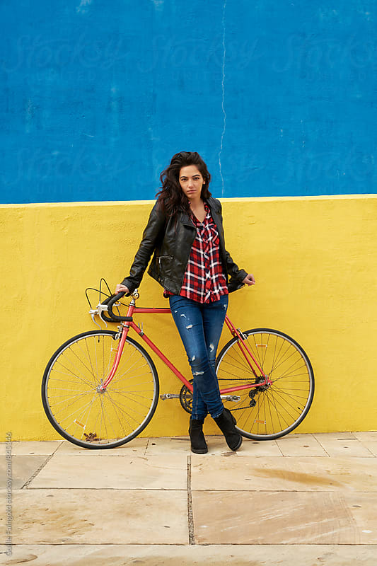 Young woman standing beside her bicycle in front of a yellow wall by Guille Faingold for Stocksy United