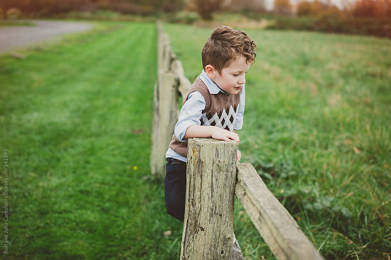 Portrait of a cute young boy climbing a fence in a field by Rob and Julia Campbell for Stocksy United