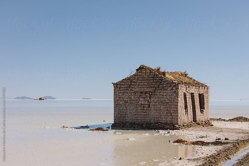 Lonely old house in shore of lake. Uyuni salt flat by Alejandro Moreno de Carlos for Stocksy United