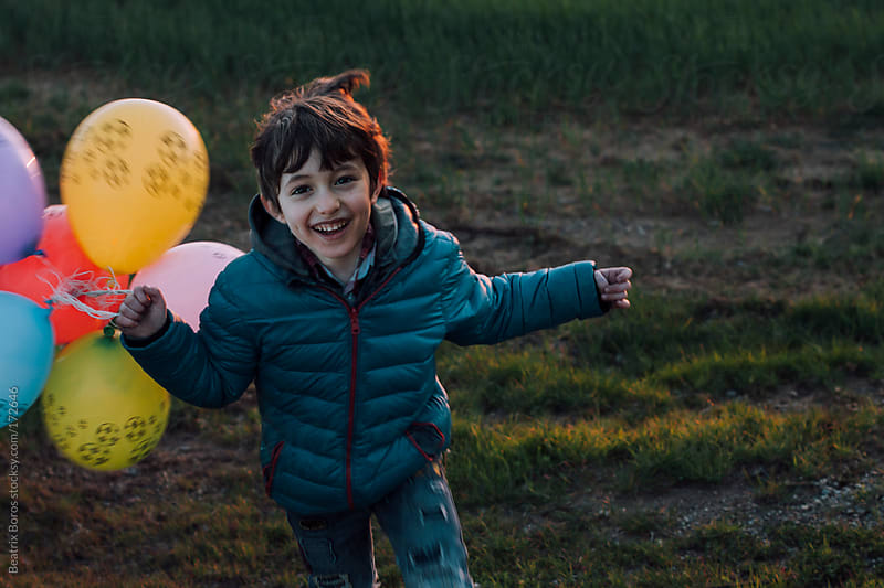 Boy running with balloons at Sunset by Beatrix Boros for Stocksy United