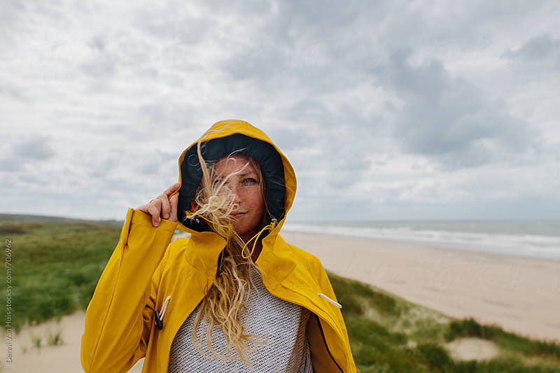 Portrait of woman on a windy beach wearing a yellow raincoat by Denni Van Huis for Stocksy United