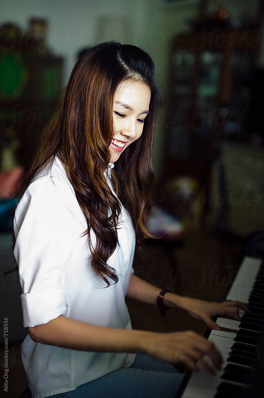 Beautiful Asian woman playing piano at home by Alita Ong for Stocksy United