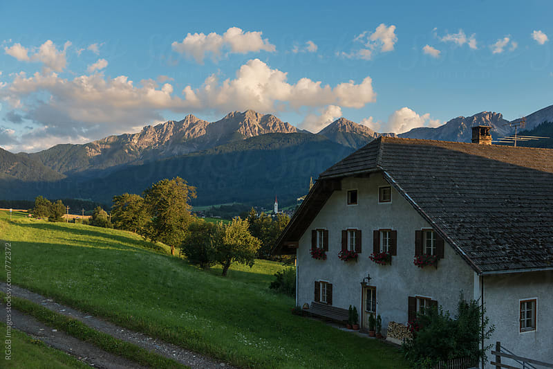 Tyrolean cottage surrounded by mountains and green hills by RG&B Images for Stocksy United