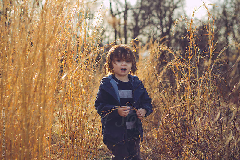 Young Boy Outside on a Trail between Tall Grass by Kevin Keller for Stocksy United