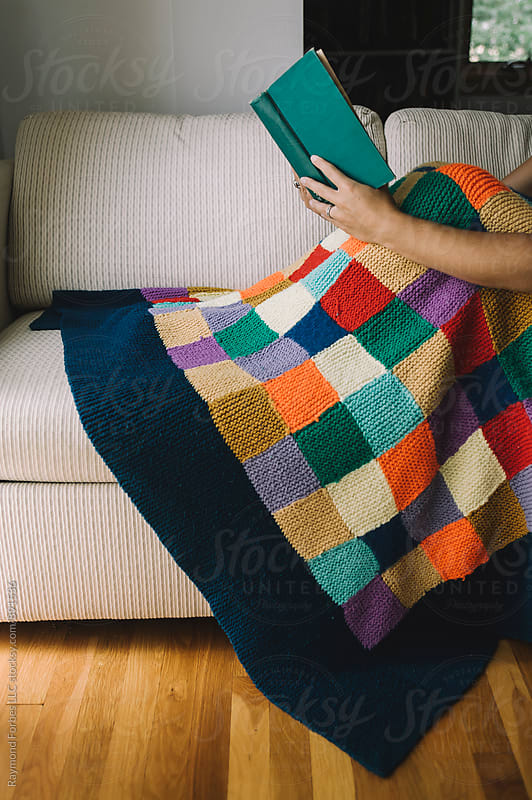 Woman reading book with Blanket by Raymond Forbes LLC for Stocksy United