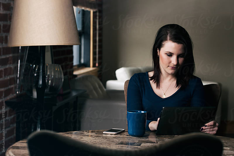 Apartment: Woman Sits Having Coffee And Reading News On Digital Tablet by Sean Locke for Stocksy United