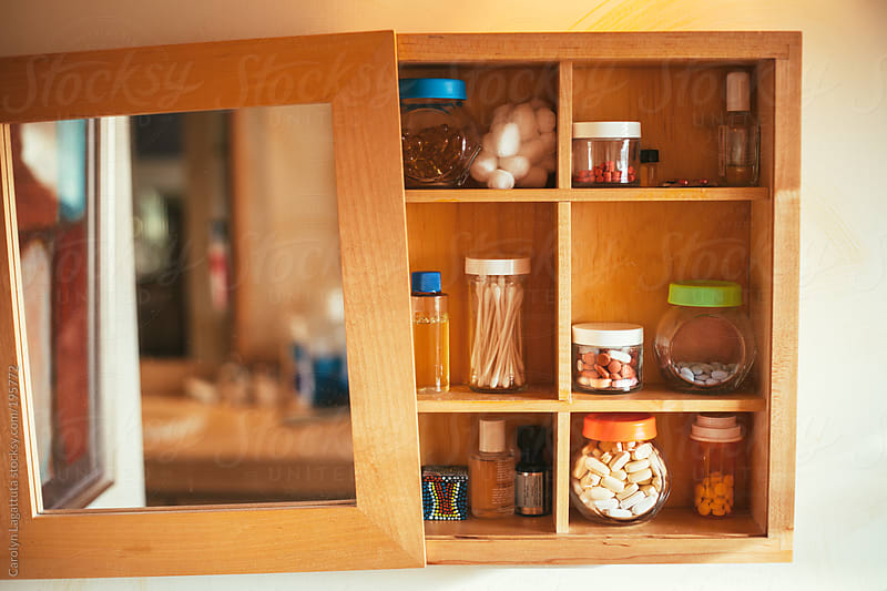 Medicine cabinet filled with vitamins, medication, oils and other bathroom items by Carolyn Lagattuta for Stocksy United