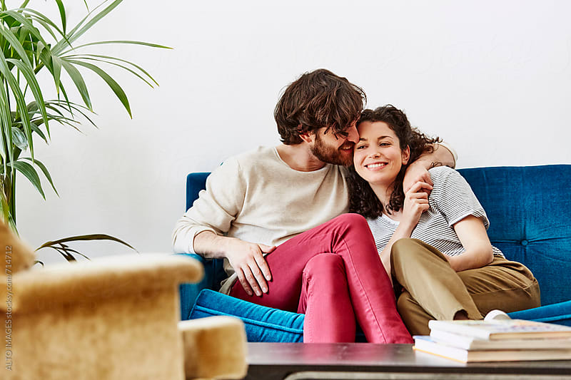 Man Kissing Woman While Sitting On Sofa by ALTO IMAGES for Stocksy United