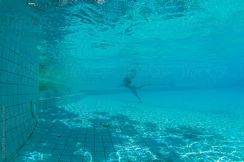Underwater view of woman in pool. by RZ CREATIVE for Stocksy United