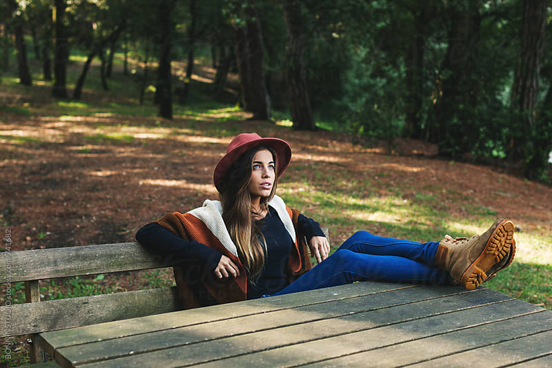 Woman sitting on a bench in the middle of the forest. by BONNINSTUDIO for Stocksy United