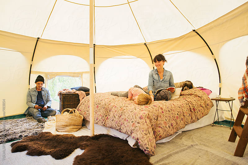 Glamping - Caucasian Family of Three Relaxing on Bed Inside Large Circular Yurt by Julien L. Balmer for Stocksy United