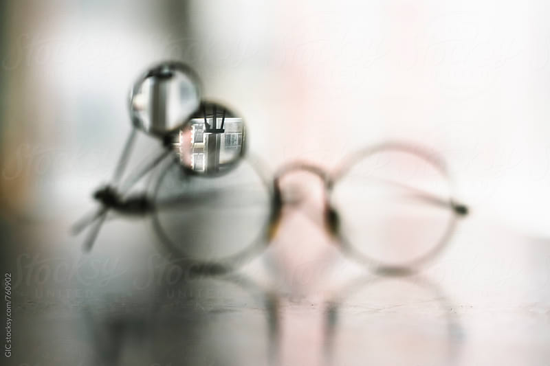 Glasses with magnifying glass by Simone Becchetti for Stocksy United
