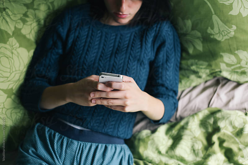 Woman browsing on her mobile phone and lying in the bed by VeaVea for Stocksy United