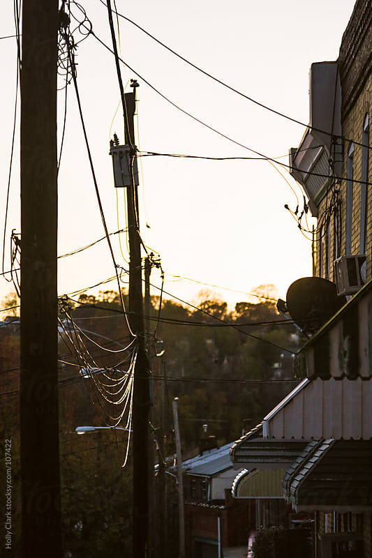 Powerlines connect to city rowhomes. by Holly Clark for Stocksy United