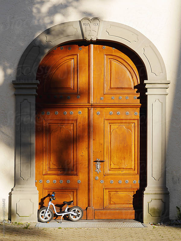 Childs bicycle outside an impressive wooden door by rolfo for Stocksy United