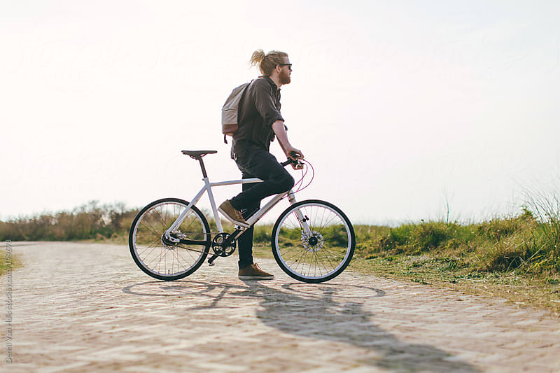 Man waiting with his bike on path in the dunes by Denni Van Huis for Stocksy United
