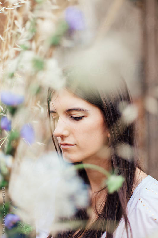 Beautiful woman seen through blurred flowers  by Laura Stolfi for Stocksy United