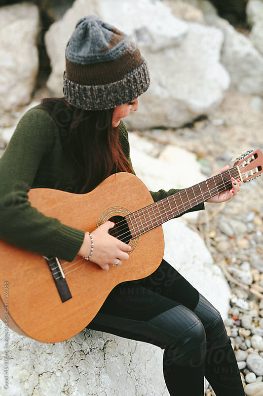 Young Woman playing guitar outdoors by Good Vibrations Images for Stocksy United