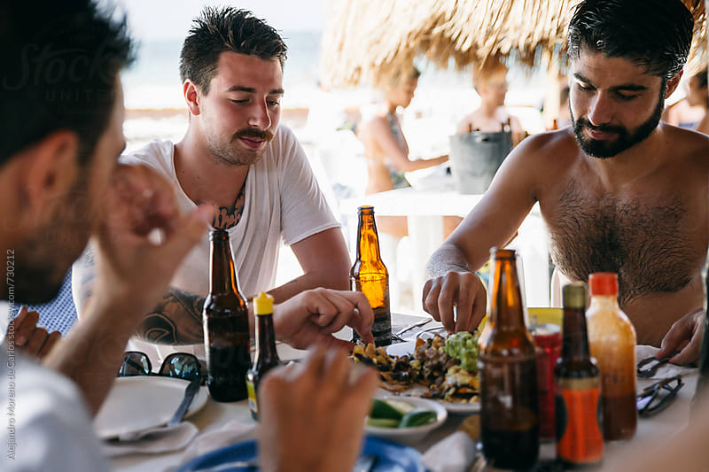 Young men friends enjoying a meal in a beach restaurant by Alejandro Moreno de Carlos for Stocksy United