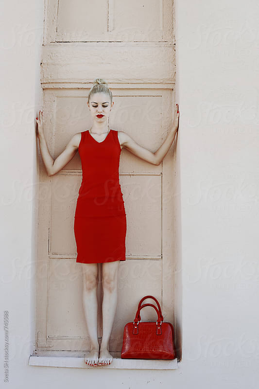 Blonde girl in a red dress by Sveta SH for Stocksy United